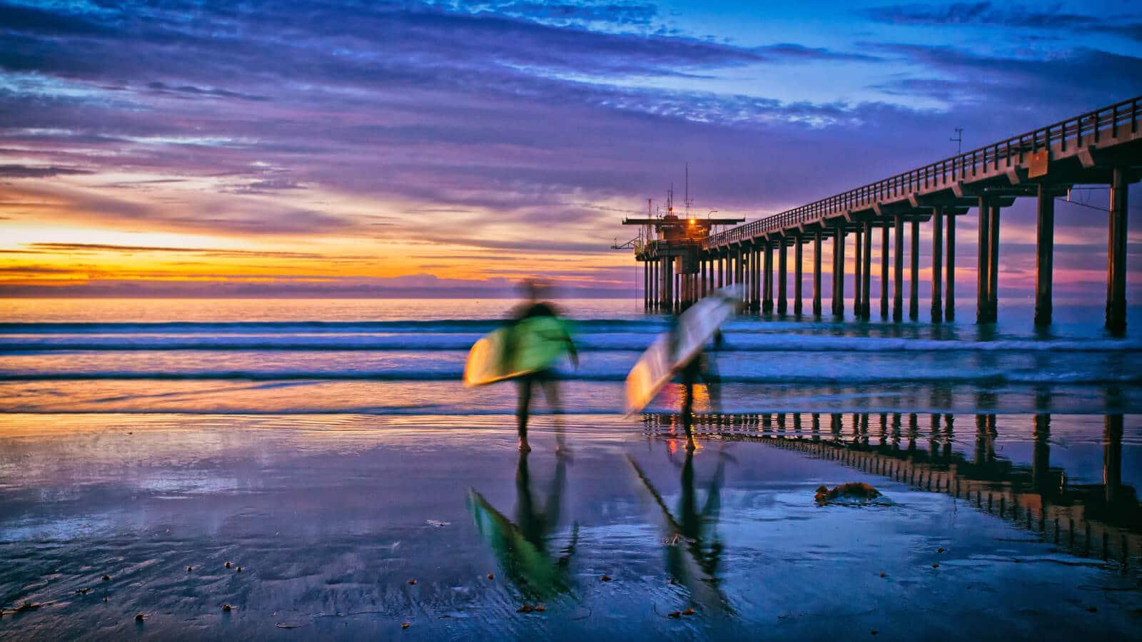 Surfers At Sunset At La Jolla Beach, San Diego, California