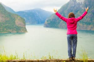 Woman With Raised Hands In Norwegian Fjords Who's In A Good Place