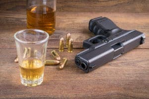 A Gun And Bullets Next To A Whiskey Representing Alcohol And Crimes