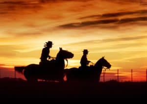 Two Cowboys On Horseback Representing Substance Abuse In Rural America