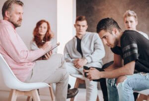 A Group Of Concerned Loved Ones Led By A Professional Interventionist Holding An Intervention For Alcoholism