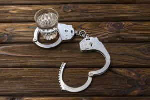 A Glass Of Alcohol In Handcuffs Representing Alcohol And Crimes