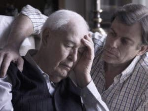An elderly man is comforted by his son as he suffers from alcohol and depression