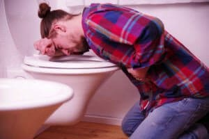 Man Throwing Up In A Toilet As A Result Of Alcohol Poisoning